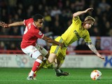 Chris Burke of Nottingham Forest is tackled by Korey Smith of Bristol City during the Sky Bet Championship match between Bristol City and Nottingham Forest at Ashton Gate on October 16, 2015 in Bristol, England.