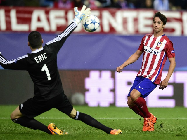 Atletico Madrid's midfielder Oliver Torres (L) shoots to score in front of Astana's Serbian goalkeeper Nenad Erich during the UEFA Champions League group C football match Club Atletico de Madrid vs FC Astana at the Vicente Calderon stadium in Madrid on Oc
