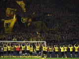 Dortmund's players celebrate with the fans after the German first division football Bundesliga match Borussia Dortmund vs FC Schalke 04 on November 8, 2015, 2015 in Dortmund, western Germany. Dortmund won the derby 3-2.