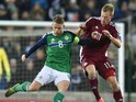 Steve Davis of Northern Ireland (L) and Eduards Visnakovs of Latvia battle for the ball during the international football friendly at Windsor Park on November 13, 2015 in Belfast, Northern Ireland.
