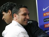 FC Barcelona's Dutch coach Frank Rijkaard says goodbye to his teammate Eusebio Sacristan holding a T-shirt that says in Catalan you 'never smoked alone' that the journalists have given to him during his last press conference as FC Barcelona coach in Camp
