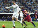 Real Madrid's Portuguese forward Cristiano Ronaldo (L) vies with Barcelona's midfielder Sergi Roberto during the Spanish league 'Clasico' football match Real Madrid CF vs FC Barcelona at the Santiago Bernabeu stadium in Madrid on November 21, 2014.
