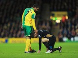 Lewis Grabban of Norwich City stands over an injured Laurent Koscielny of Arsenal during the Barclays Premier League match between Norwich City and Arsenal at Carrow Road on November 29, 2015
