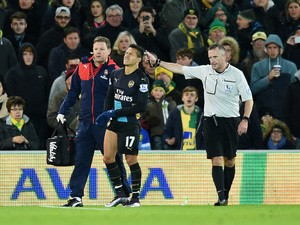 An injured Alexis Sanchez of Arsenal (17) is given assistance during the Barclays Premier League match between Norwich City and Arsenal at Carrow Road on November 29, 2015