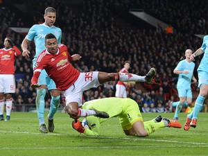 PSV Eindhoven's Dutch goalkeeper Jeroen Zoet (Below) defends the ball from Manchester United's English midfielder Jesse Lingard (3rd L) during their UEFA Champions League Group B football match between Manchester United and PSV Eindhoven at Old Trafford S