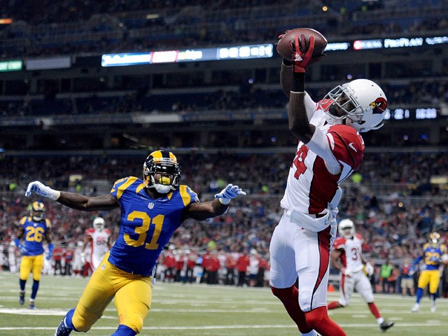 J.J. Nelson #14 of the Arizona Cardinals catches a pass for a touchdown while under pressure from Maurice Alexander #31 of the St. Louis Rams in the first quarter at the Edward Jones Dome on December 6, 2015