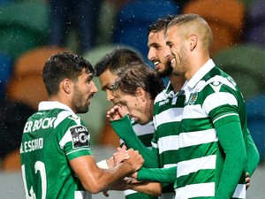 Sporting's Algerian forward Islam Slimani (R) celebrates with his teammates after scoring during the Portuguese league football match Sporting CP vs Moreirense FC at the Jose Alvalade stadium in Lisbon on December 13, 2015