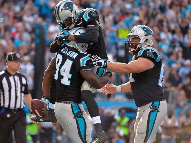 Ed Dickson #84 of the Carolina Panthers celebrates with teammates after making a touchdown catch against the Atlanta Falcons during their game at Bank of America Stadium on December 13, 2015