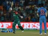 Bangladesh's Mushfiqur Rahim celebrates after scoring a boundary as Indian bowler Hardik Panday looks on on March 23, 2016