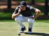 Rory McIlroy squats to line up a shot during the first round of The Masters on April 7, 2016