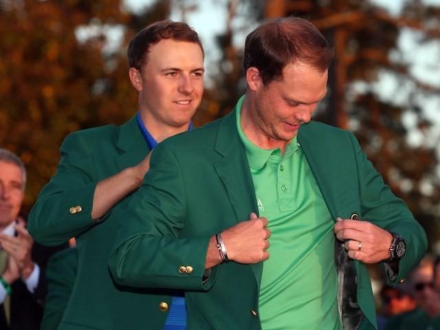 Jordan Spieth hands Danny Willett his green jacket at The Masters on April 10, 2016