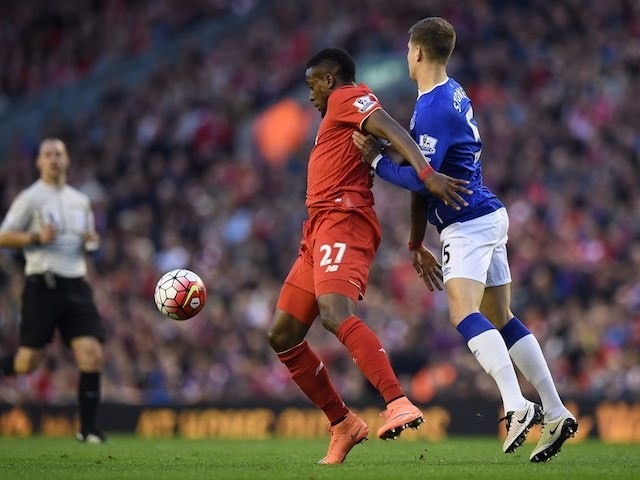 Divock Origi fends off the advances of big John Stones during the Premier League game between Liverpool and Everton on April 20, 2016