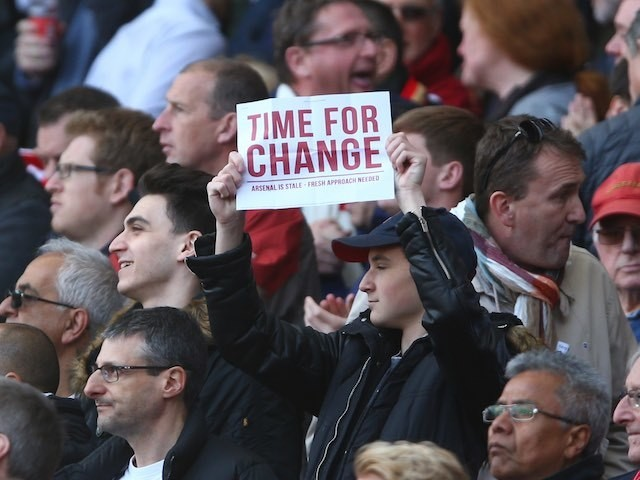 A fan holds up an itimidating piece of A4 paper in protest at Arsene Wenger during the Premier League game between Arsenal and Norwich City on April 30, 2016