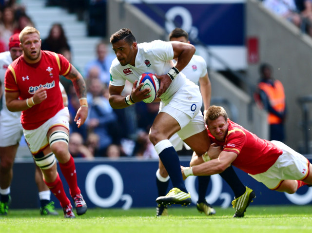 England centre Luther Burrell powers through the tackle of Wales fly-half Dan Biggar en route to scoring the opening try of their match against Wales at Twickenham on May 29, 2016