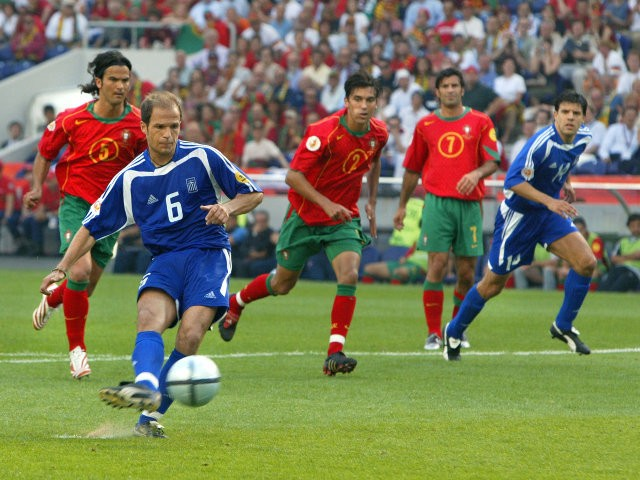 Greece's midfielder Angelis Basinas (foreground) kicks the ball to score 12 June 2004 at Dragao stadium in Porto during the Euro 2004 group A football match between Portugal and Greece at the European Nations championship in Portugal.