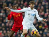 Swansea City striker Fernando Llorente holds off the challenge of Georginio Wijnaldum during his side's Premier League clash with Liverpool at Anfield on January 21, 2017