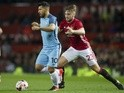 Luke Shaw and Sergio Aguero in action in the match between Manchester United and Manchester City on October 26, 2016