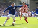 Wayne Rooney fends off Geoff Cameron during the Premier League game between Everton and Stoke City on August 12, 2017